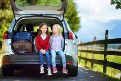 Entzückendes wenig Sitzen zwei in einem Auto bevor dem Gehen auf Ferien mit ihren Eltern Lizenzfreies Stockfoto