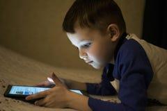 Entz?ckender kleiner Junge, der auf einer digitalen Tablette spielt Junge, der digitale Tablette betrachtet Elterliche Erlaubnisk lizenzfreie stockfotos