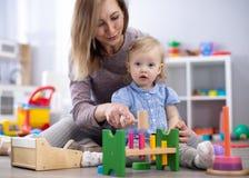 Entz?ckendes Baby, das mit p?dagogischen Spielwaren in der Kindertagesst?tte spielt Gl?ckliches gesundes Kind, das Spa? mit bunte stockfoto