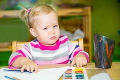 Entzückende Kindermädchenzeichnung mit bunten Bleistiften im Kindertagesstättenraum Kind im Kindergarten in der Montessori-Vorsch Lizenzfreie Stockbilder