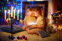 Entzückende kleine Mädchen, die ein magisches Weihnachtsgeschenk öffnen Lizenzfreie Stockfotografie