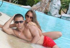 Entzückende Paare am Swimmingpool Stockfoto