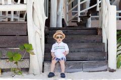 Entzückender Kleinkindjunge, der auf den Treppen sitzt Stockbild