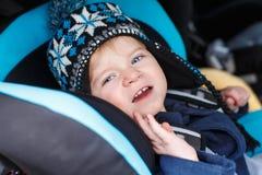 Entzückender Kleinkindjunge, der im Sicherheitsautositz sitzt Stockfotos