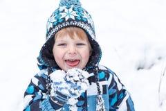 Entzückender Kleinkindjunge, der Spaß mit Schnee am Wintertag hat Stockfoto