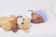 Entzückendes Baby, das friedlich mit Teddybären schläft Stockbilder