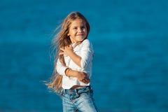 Entzückendes glückliches lächelndes kleines Mädchen auf Strand Stockfoto