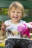 Entzückendes jähriges Baby, das auf einer Bank mit einer Puppe I sitzt Lizenzfreies Stockfoto