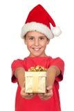 Entzückendes Kind mit dem Sankt-Hut, der ein Geschenk anbietet Lizenzfreie Stockfotografie