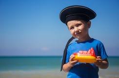 Entzückendes Kind mit Spielzeugboot gegen das Meer am sonnigen Tag Stockfotografie