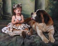 Entzückendes Kind und ihr Bernhardiner-Welpen-Hund Lizenzfreie Stockbilder