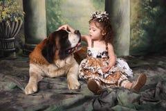 Entzückendes Kind und ihr Bernhardiner-Welpen-Hund Lizenzfreies Stockfoto