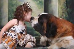 Entzückendes Kind und ihr Bernhardiner-Welpen-Hund Stockfotos