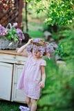 Entzückendes Kindermädchen, das im Frühjahr lila Kranz im rosa Plaidkleid nahe Garten des Weinlesebüros trägt Stockbilder