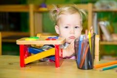 Entzückendes Kindermädchen, das mit pädagogischen Spielwaren im Kindertagesstättenraum spielt Kind im Kindergarten in der Montess Lizenzfreie Stockfotos