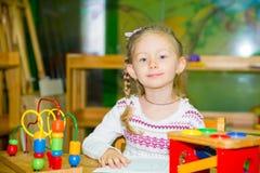 Entzückendes Kindermädchen, das mit pädagogischen Spielwaren im Kindertagesstättenraum spielt Kind im Kindergarten in der Montess Stockfotos