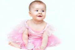 Entzückendes kleines Baby im rosa Kleid, das mit ihrem rosa Schuh spielt Lizenzfreies Stockfoto