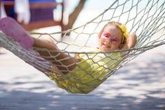 Entzückendes kleines Mädchen auf den tropischen Ferien entspannend Stockfoto