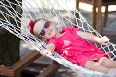 Entzückendes kleines Mädchen auf den tropischen Ferien entspannend Stockfotografie