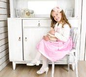 Entzückendes kleines Mädchen, das auf Stuhl mit Geschenkbox sitzt Stockbild