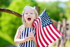 Entzückendes kleines Mädchen, das draußen amerikanische Flagge am schönen Sommertag hält Lizenzfreie Stockfotos