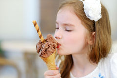 Entzückendes kleines Mädchen, das draußen geschmackvolle frische Eiscreme isst Stockfotografie