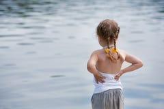 Entzückendes kleines Mädchen, das durchdacht auf dem Fluss schaut Lizenzfreies Stockfoto