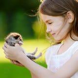 Entzückendes kleines Mädchen, das mit kleinem Kätzchen spielt Lizenzfreies Stockbild
