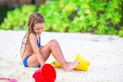 Entzückendes kleines Mädchen, das mit Strandspielwaren spielt Stockfoto