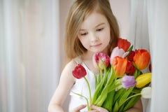 Entzückendes kleines Mädchen mit Tulpen am Fenster Stockfoto