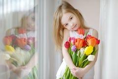 Entzückendes kleines Mädchen mit Tulpen am Fenster Stockfotografie
