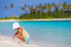 Entzückendes kleines Mädchen am Strand während der Sommerferienzeichnung auf Sand Lizenzfreies Stockfoto