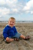 Entzückendes Kleinkindbaby, das im Sand spielt Stockfoto
