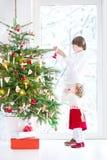 Entzückendes Kleinkindmädchen, das ihrem Bruder hilft, einen schönen Weihnachtsbaum zu verzieren Lizenzfreies Stockfoto