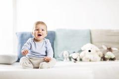 Entzückendes lachendes Baby, das auf Sofa sitzt und oben schaut. Lizenzfreie Stockfotos