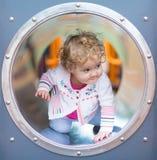Entzückendes lustiges Baby, das auf einem Spielplatz sich versteckt Stockfoto