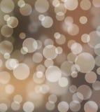 Entziehen Sie glühenden Bokeh Hintergrund in den braunen Farbtönen Stockbilder