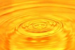 entziehen Sie Hintergrund Ein Wassertropfen fällt in Gold Lizenzfreies Stockbild