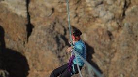Envían el escalador de la mujer encima de la cuerda a través del abismo almacen de metraje de vídeo