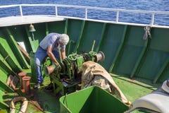 Envíe el mecanismo del chigre del ancla de la reparación del trabajador con la cadena Foto de archivo
