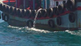 Envíe la flotación con los neumáticos de coche a bordo el agua del dren en el mar azul Barco flotante en agua de mar de la turque almacen de metraje de vídeo