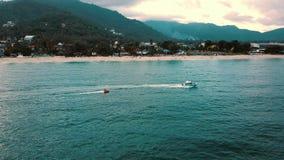 Envíe a la gente de los turistas del montar a caballo en la opinión aérea del barco de plátano Atracción de la agua de mar almacen de metraje de vídeo