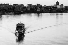 Envíe la navegación en agua con la ciudad en el fondo fotos de archivo libres de regalías