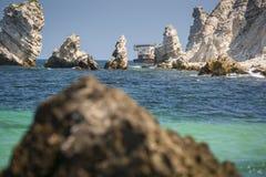 Envíe la ruina detrás de las rocas agudas en el mar debajo del cielo fotos de archivo libres de regalías