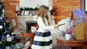 Envíe a Santa Claus, la pequeña muchacha dulce hace un deseo, lanza una letra para Papá Noel en el buzón, el niño es feliz y metrajes