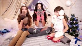 Envíe un beso del aire con la enhorabuena de la Feliz Navidad, saludos del ` s del Año Nuevo a partir de tres hermanas, muchachas metrajes