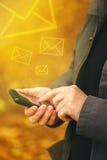 Envío de los mensajes de SMS en el teléfono móvil en otoño Fotos de archivo libres de regalías