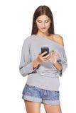 Envío de mensajes de texto adolescente de la muchacha en su móvil Fotos de archivo libres de regalías