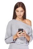 Envío de mensajes de texto adolescente de la muchacha en su móvil Imagen de archivo libre de regalías