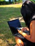 Envío de mensajes de texto adolescente de la muchacha mientras que usa la computadora portátil Fotografía de archivo libre de regalías